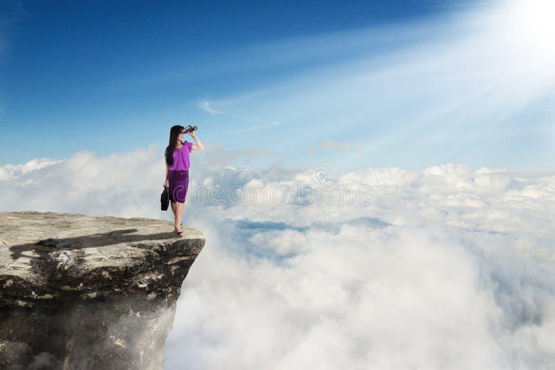 Junge Geschäftsfrau mit Ferngläsern auf Klippe stockbilder