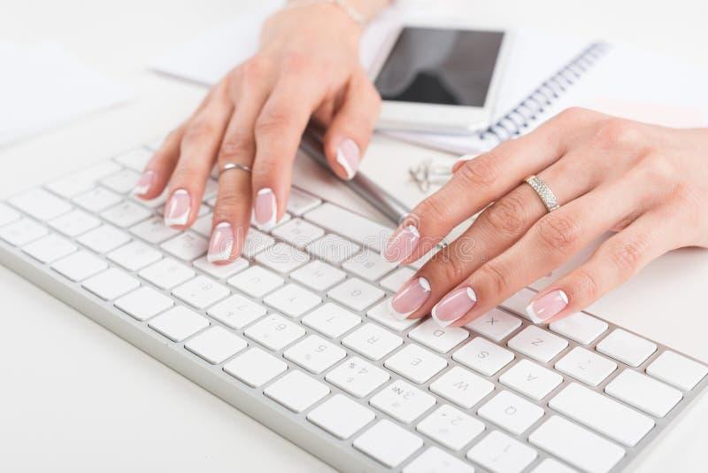 Junge Geschäftsfrau mit schöner Maniküre schreibend auf Tastatur am Arbeitsplatz lizenzfreie stockfotografie