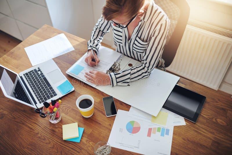 Junge Geschäftsfrau stark bei der Arbeit an ihrem Schreibtisch stockfoto