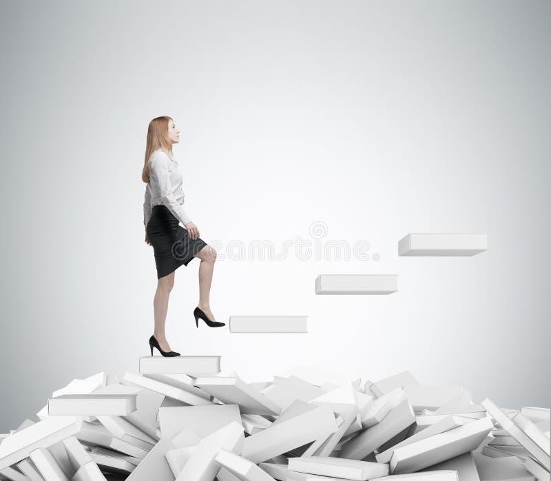 Junge Geschäftsfrau steigt zur Treppe Ein Konzept des Bildungsprozesses lizenzfreie stockfotos