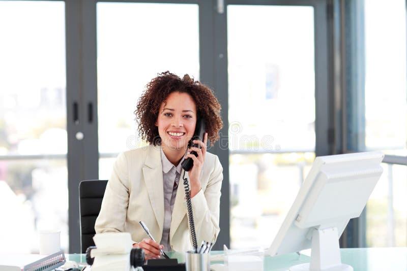 Junge Geschäftsfrau am Telefon lizenzfreie stockfotografie