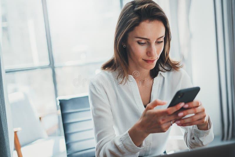 Junge Gesch?ftsfrau unter Verwendung des Mobilhandys an ihrem Arbeitsplatz im modernen B?ro Unscharfer Hintergrund lizenzfreie stockfotos