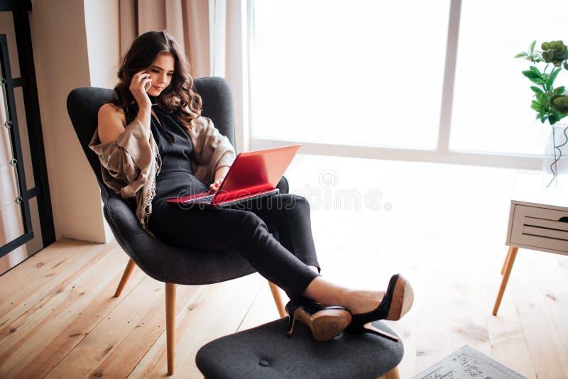 Junge Geschäftsfrauarbeit zu Hause Sitzen Sie in den Stuhl- und Griffbeinen auf kleinem Schemel Unterhaltung am Telefon und Anwen lizenzfreies stockbild