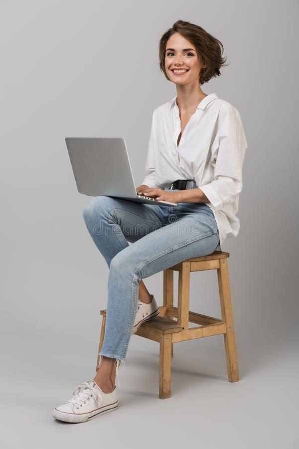 Junge Geschäftsfrauaufstellung lokalisiert über dem grauen Wandhintergrund, der auf Schemel unter Verwendung der Laptop-Computers lizenzfreie stockfotos
