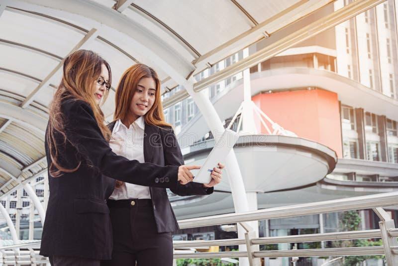 junge Geschäftsfrauen, die Tablet-Computer an der Stadt verwenden lizenzfreie stockfotografie