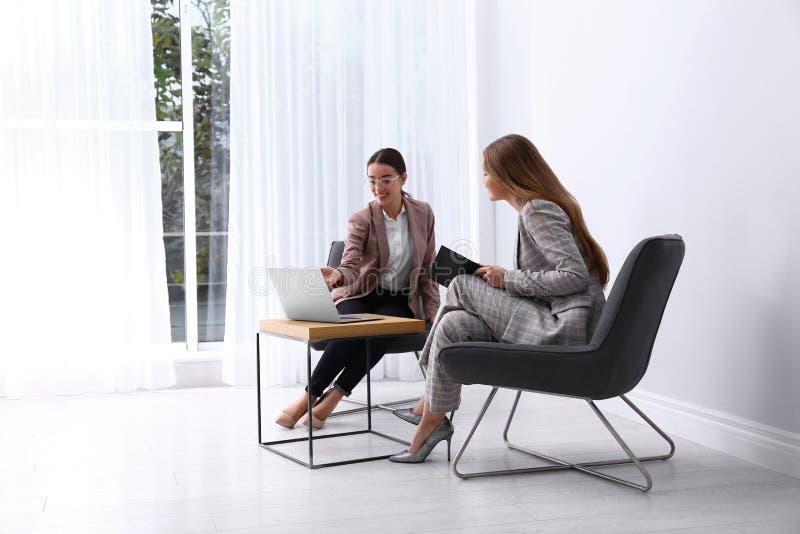 Junge Geschäftsfrauen sitzen in Sesseln am Tisch stockfotos