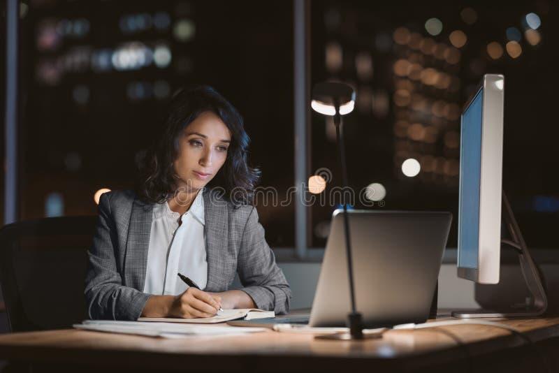 Junge Geschäftsfrauschreibensanmerkungen in einem Büro nachts stockfotos