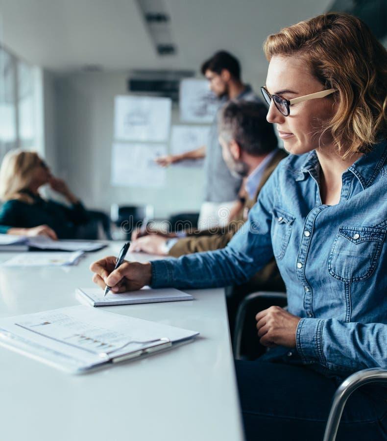 Junge Geschäftsfrauschreibensanmerkungen während der Darstellung lizenzfreie stockfotografie