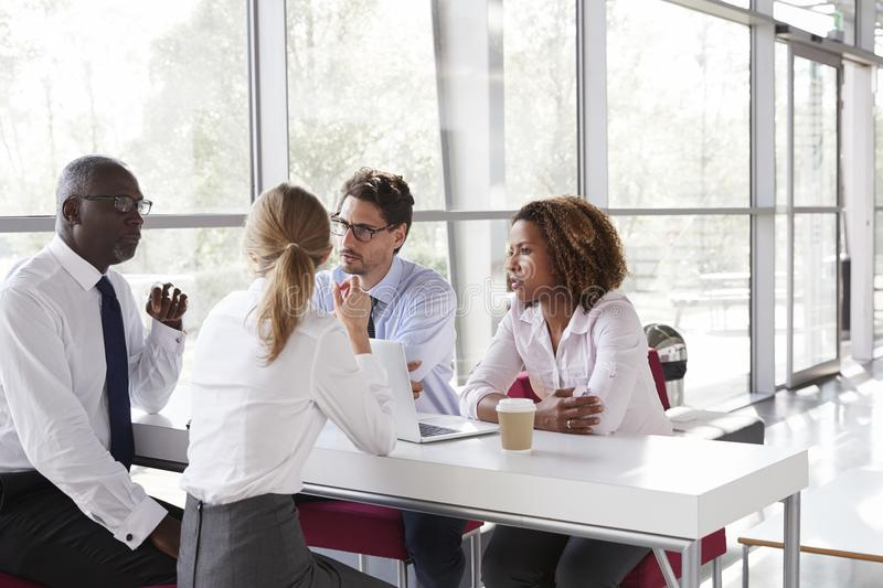 Junge Geschäftsleute, die über Kaffee in einer modernen Lobby sprechen stockfoto