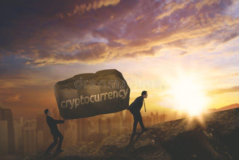 Junge Geschäftsleute, die cryptocurrency Wort anheben stockfotos