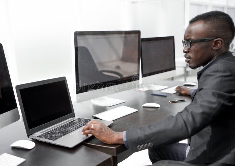 Junge Geschäftsleute, die an einem Computer im Computerraum arbeiten stockfotografie