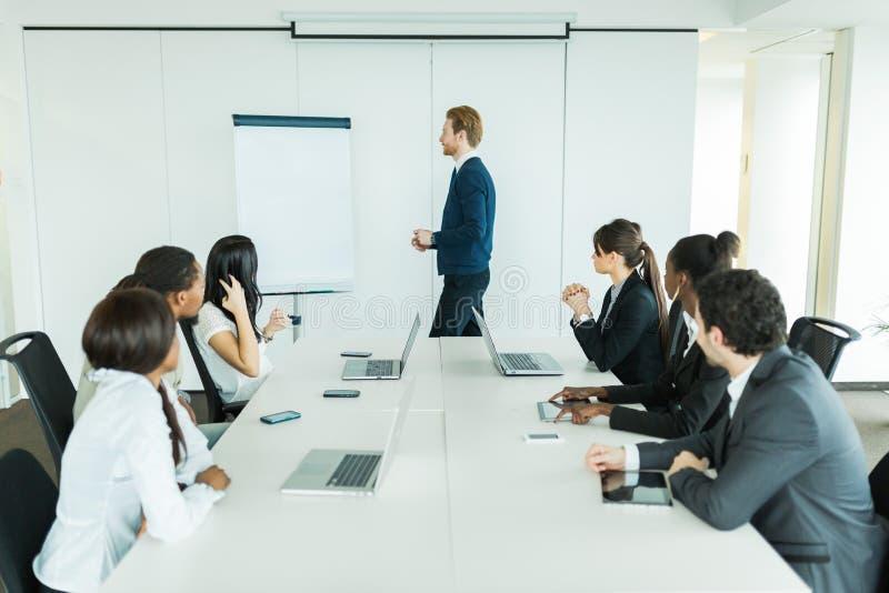 Junge Geschäftsleute, die an einem Konferenztische und einem Lernen sitzen stockfotografie