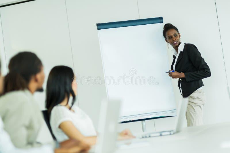 Junge Geschäftsleute, die an einem Konferenztische und einem Lernen sitzen lizenzfreie stockbilder