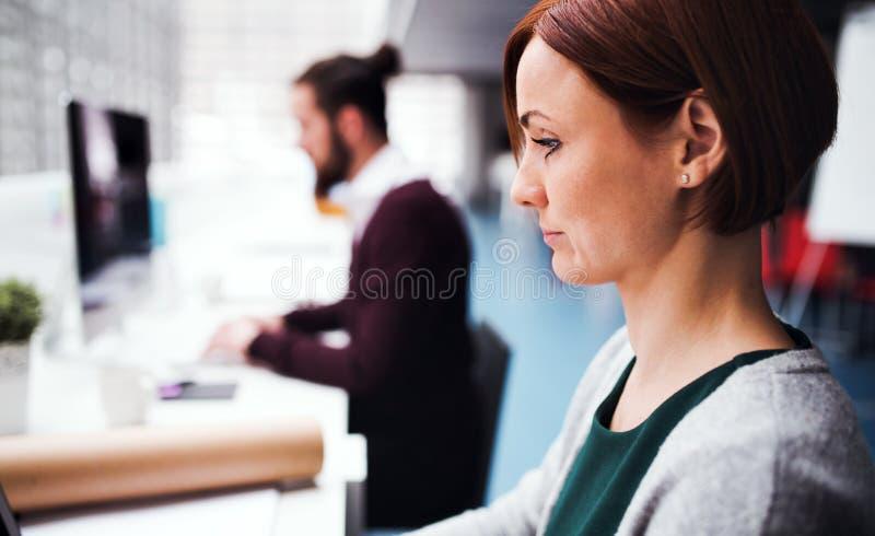 Junge Geschäftsleute, die im Büro, unter Verwendung des Computers arbeiten lizenzfreie stockfotos