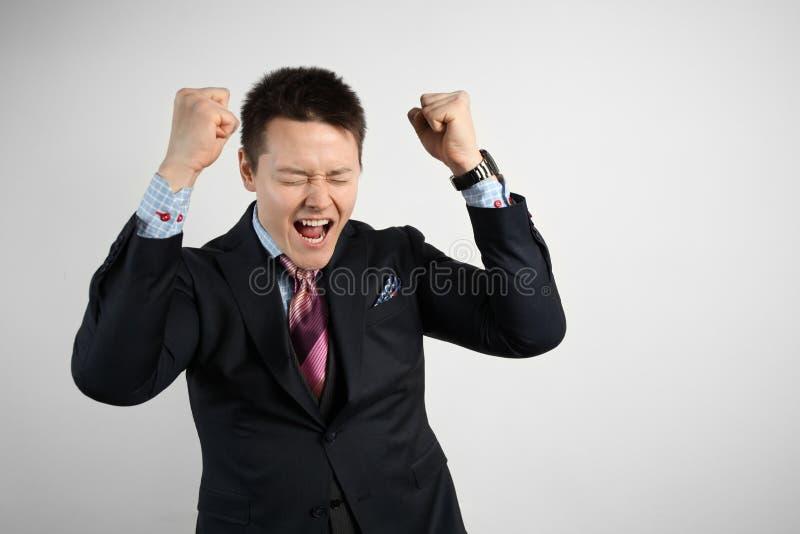 Junge Geschäftsleute in einem Anzug auf grauem Hintergrund feiern Sieg und Erfolg Glücklich und aufgeregt ausdrücken stockfoto