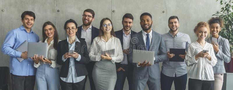 Junge Geschäftsleute mit unterschiedlichen Gadgets, die sich im Büro positionieren stockbild