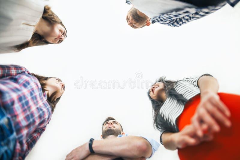 Junge Geschäftsleute stehen in einem Kreis und betrachten einander lizenzfreie stockfotos