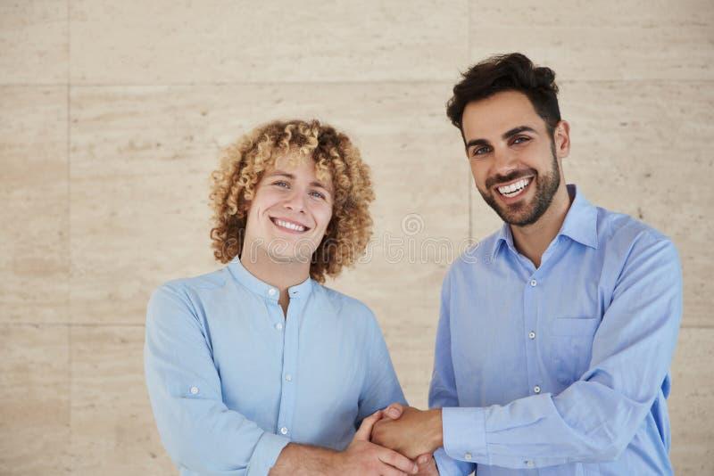 Junge Geschäftsmänner, die Handdas lächeln rütteln stockfotografie