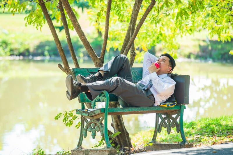 Junge Geschäftsmänner stehen auf Stühlen still und essen Äpfel nachher lizenzfreie stockfotos
