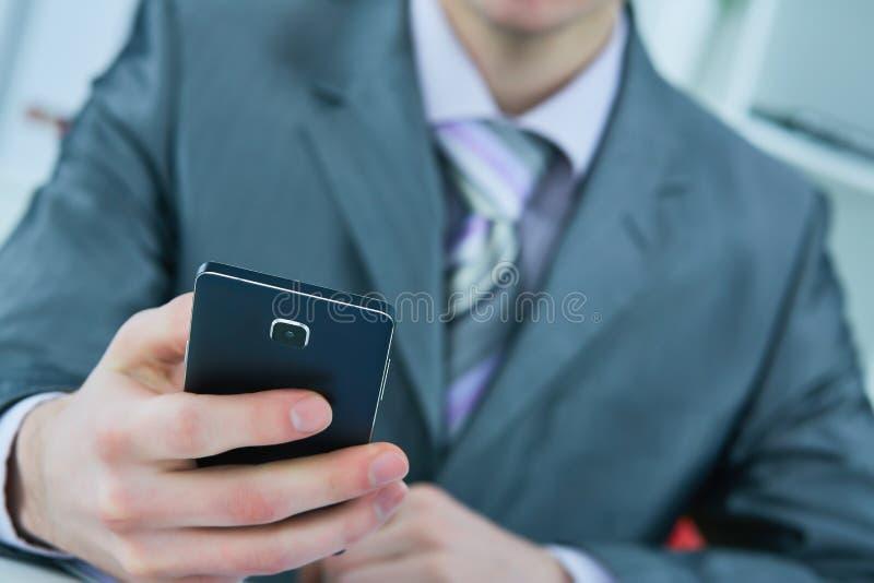 Junge Geschäftsmann-Lesemitteilung mit Smartphone im Büro lizenzfreie stockfotos