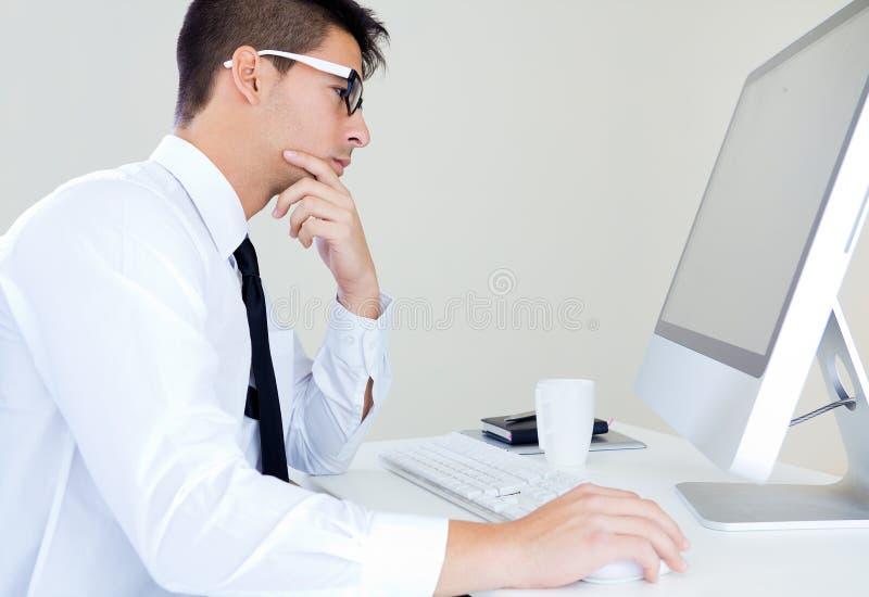Junge Geschäftsmannarbeit im modernen Büro auf Computer lizenzfreies stockbild