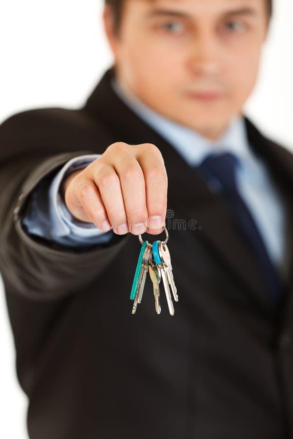 Junge Geschäftsmannholdingtasten in der Hand getrennt lizenzfreie stockfotos