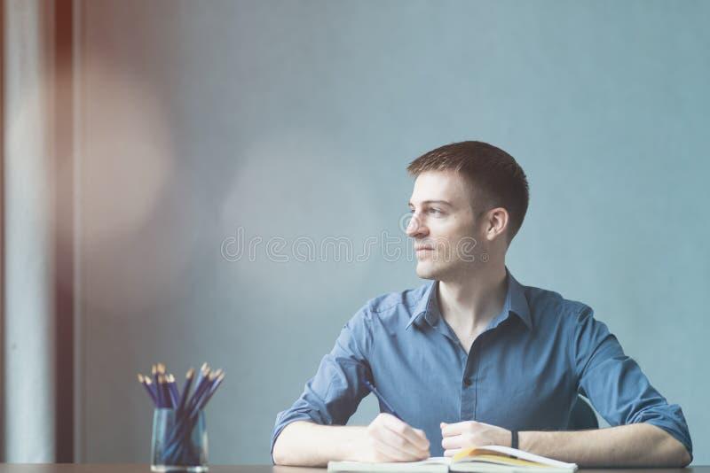 Junge Geschäftsmannkaukasier, die am Schreibtischbürotisch sitzen und Kenntnisse im Notizbuch nehmen Das Fenster heraus schreiben lizenzfreie stockfotografie