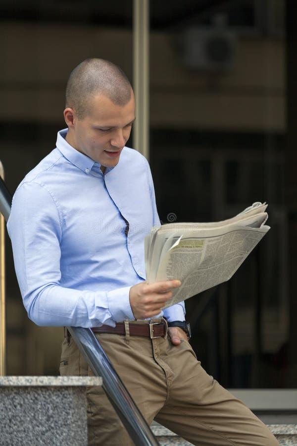 Junge Geschäftsmannstellung und gelesene Zeitungen stockfotos