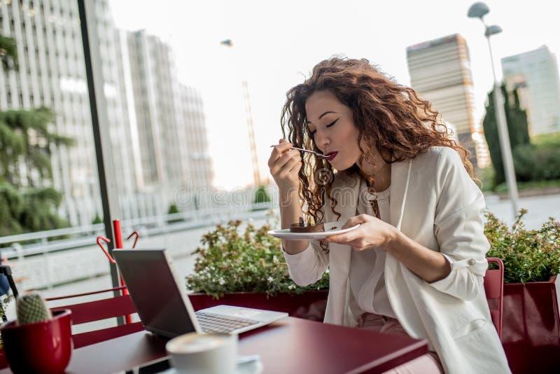 Junge Geschäftsrothaarigefrau auf dem Computer und dem Essen eines Kuchens stockfotografie