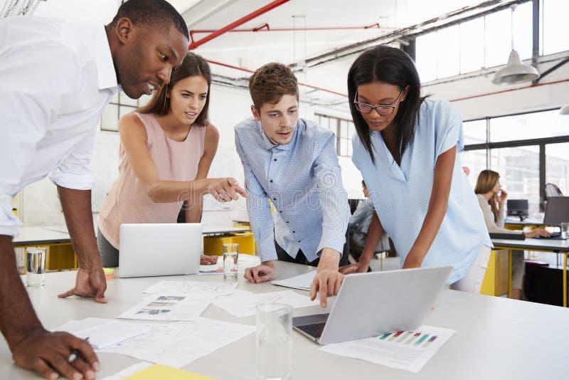 Junge Geschäftsteamarbeit, die am Schreibtisch in einem beschäftigten Büro steht lizenzfreies stockbild