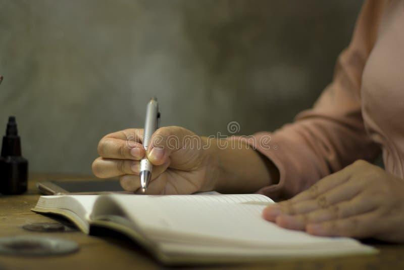 Junge Gesch?ftsfrau, die mit einem Stift im B?ro, sie ?ber die Zeit hinaus bleibend arbeitet lizenzfreies stockbild