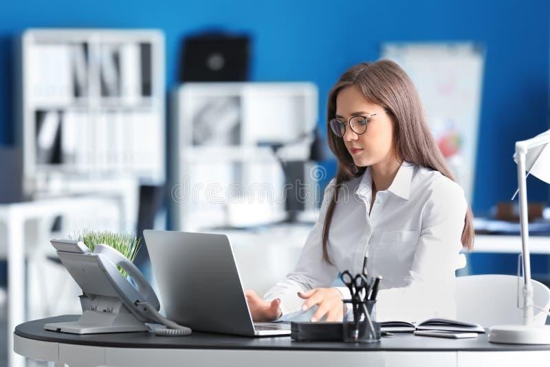 Junge Gesch?ftsfrau, die mit Laptop im B?ro arbeitet stockfotos