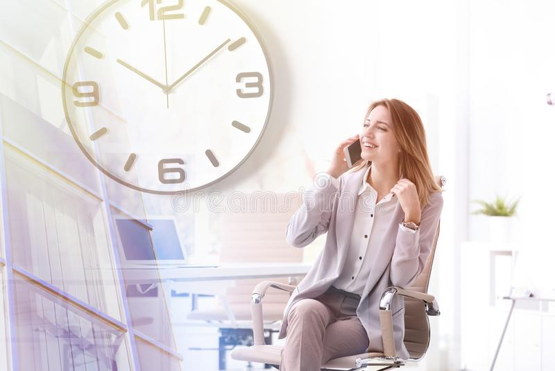Junge Gesch?ftsfrau mit dem intelligenten Telefon, das im B?rostuhl am Arbeitsplatz sitzt lizenzfreie stockbilder