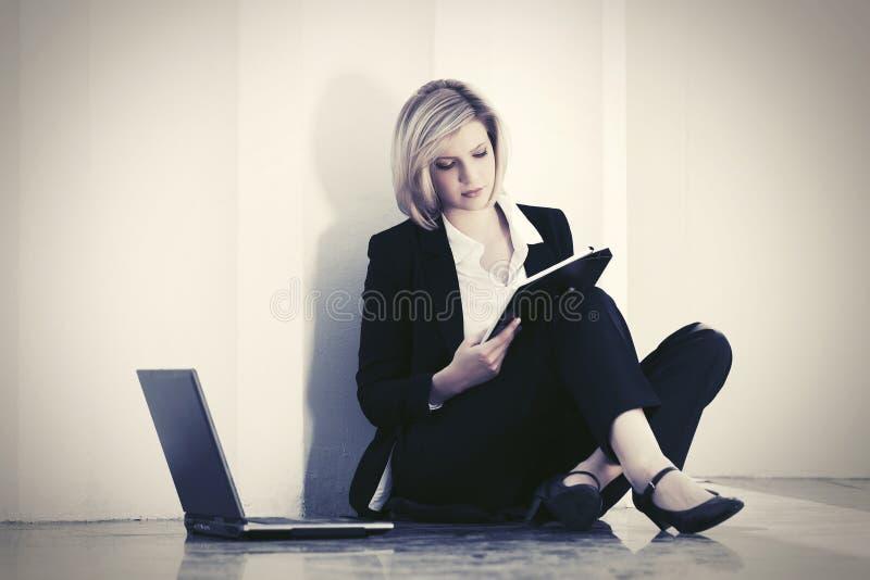 Junge Gesch?ftsfrau mit dem Laptop, der an der Wand sitzt lizenzfreies stockfoto