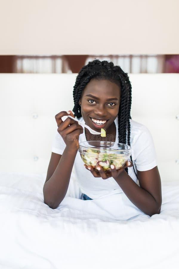 Junge gesunde afrikanische Frau, die auf Bett sitzt und Salat isst lizenzfreies stockfoto