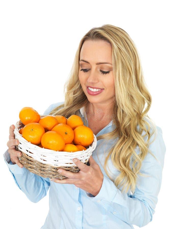 Junge gesunde attraktive Frau, die einen Korb von Tangerinen hält stockfotografie