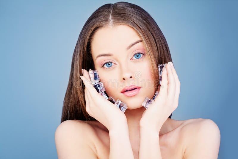 Junge gesunde Frau, die Eis-Würfel hält Badekurort Skincare-Konzept stockbilder