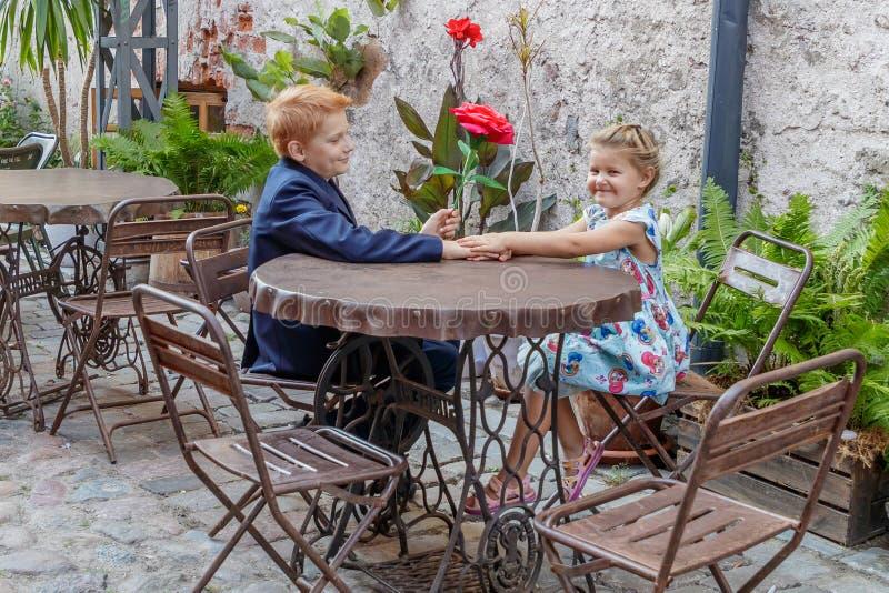 Junge gibt Mädchen eine rote Blume stockbild