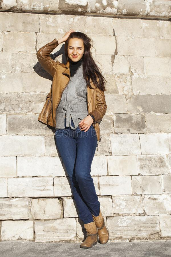 Junge glückliche Frau in der braunen Lederjacke stockfotos