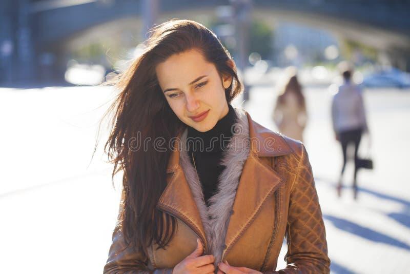 Junge glückliche Frau in der braunen Lederjacke lizenzfreie stockfotos