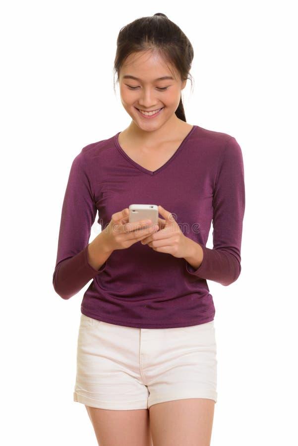 Junge glückliche asiatische Jugendliche, die Handy lächelt und verwendet lizenzfreie stockfotos