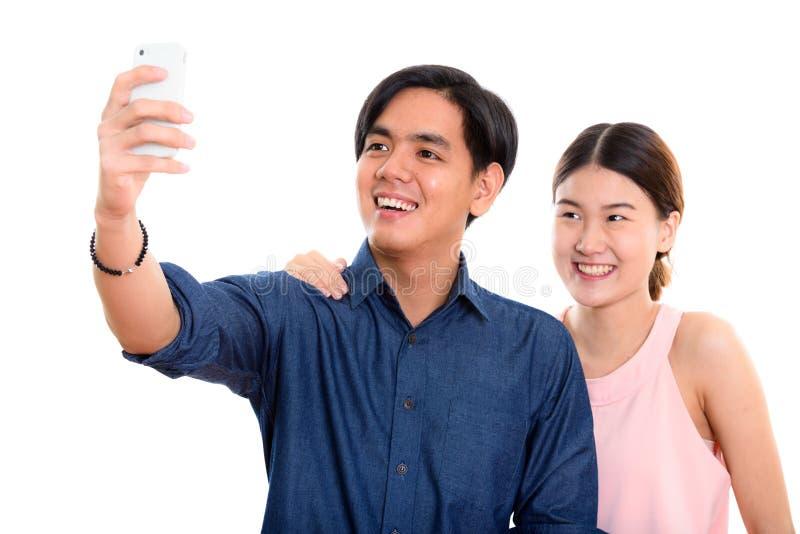 Junge glückliche asiatische lächelnde Paare beim Nehmen des selfie Bildesprits lizenzfreie stockbilder