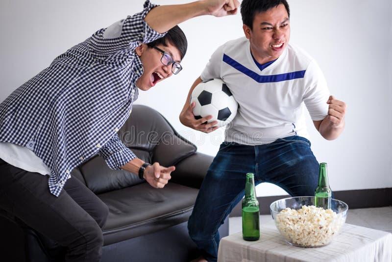 Junge glückliche asiatische Männer Familie oder Fußballfane, die Fußball MA aufpassen stockbild