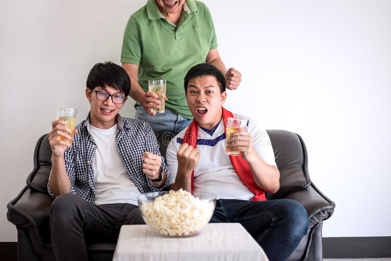 Junge glückliche asiatische Männer Familie oder Fußballfane, die Fußball MA aufpassen stockbilder
