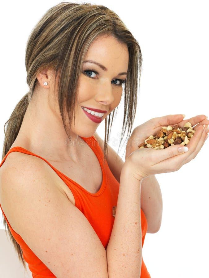 Junge glückliche attraktive Frau, die eine Handvoll Mischnüsse hält lizenzfreies stockbild