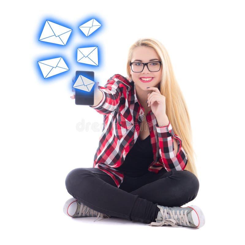 Junge glückliche blondie Frau, die sms von beweglichem pH sitzt und sendet stockfotografie