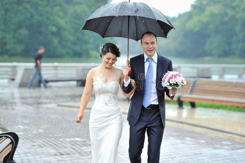 Junge glückliche Braut und Bräutigam, die durch den Regen geht stockfotos