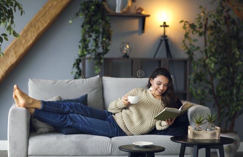 Junge glückliche brunette Frau mit tragender Strickjacke des Buches stockfotografie