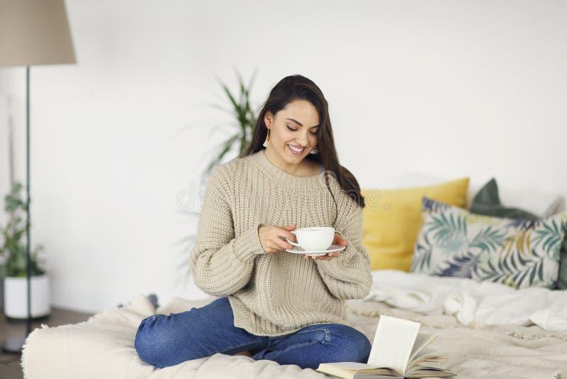 Junge glückliche brunette Frau mit tragender Strickjacke des Buches stockbilder