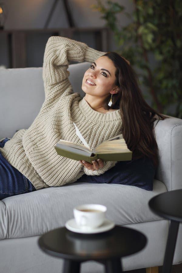 Junge glückliche brunette Frau mit tragender Strickjacke des Buches stockbild